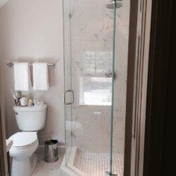 Glass door corner shower in remodeled bathroom