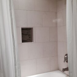 White tile bath/shower combo in finished basement bathroom