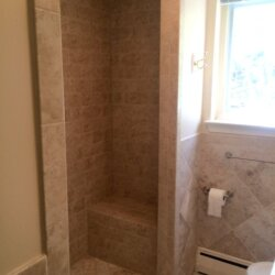Beige tile shower with built-in bench
