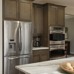 Remodeled kitchen featuring stainless steel refrigerator and double stacked oven