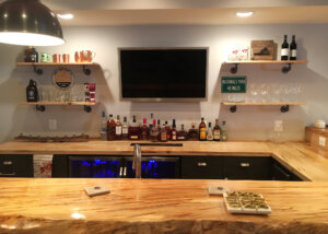 Home bar in finished basement with natural edge wood bar top