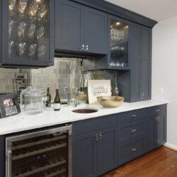 Wine bar with dark blue cabinets and mirrored backsplash
