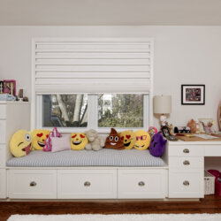 Child's bedroom window with emoji pillows