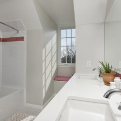 Bathroom with red accent tiles and two faucets