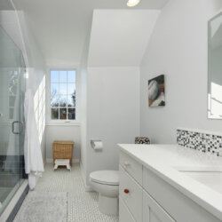White tile bathroom with black accent tiles