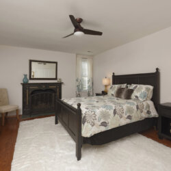 Guest bedroom with fireplace and white rug