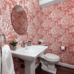 Bathroom with distinctive pink and white patterned wallpaper
