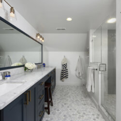 Master bathroom with white marble sinks and gray tiles