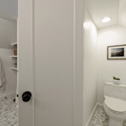 White tile bathroom with separate toilet stall