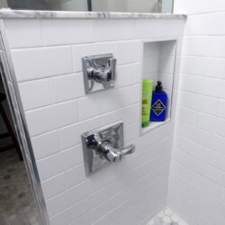 Stainless steel fixtures in white tile open shower