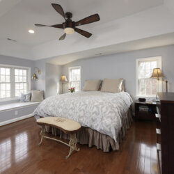 Light blue master bedroom with wood ceiling fan