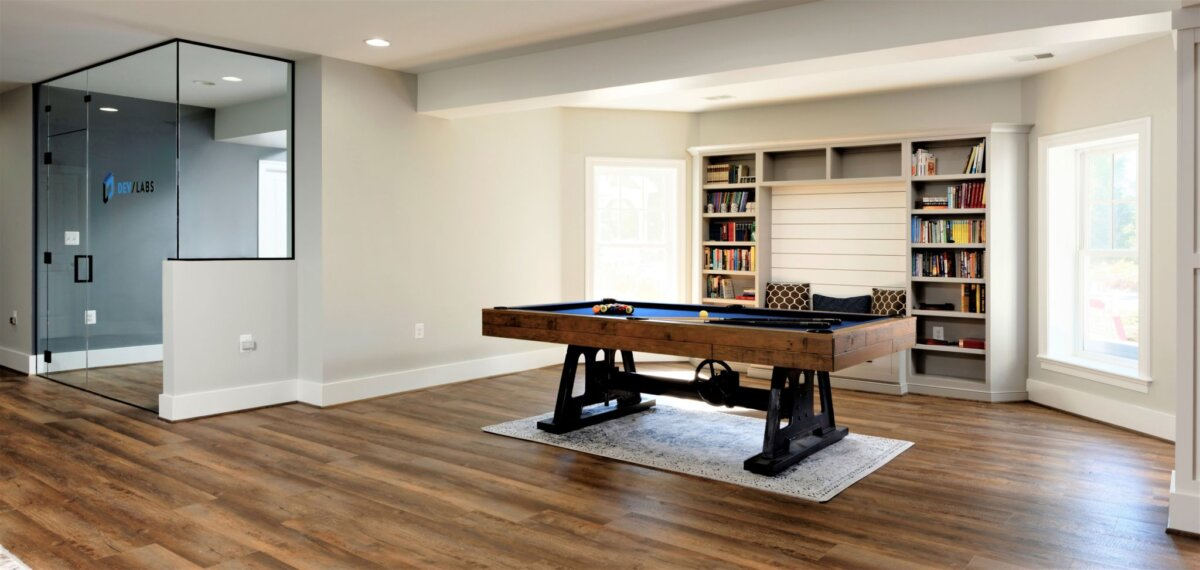 basement with glass wall and pool table book shelves