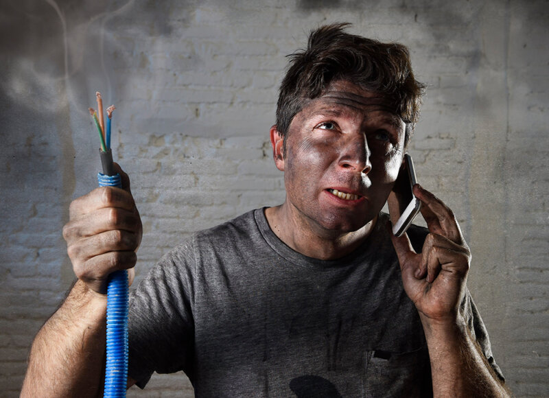 man holding smoking wires from DIY home improvement project