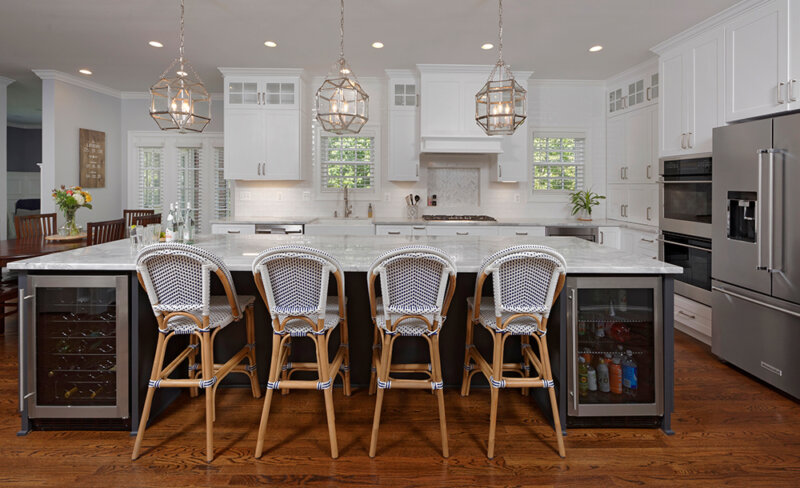 large kitchen island with refrigerators and chairs